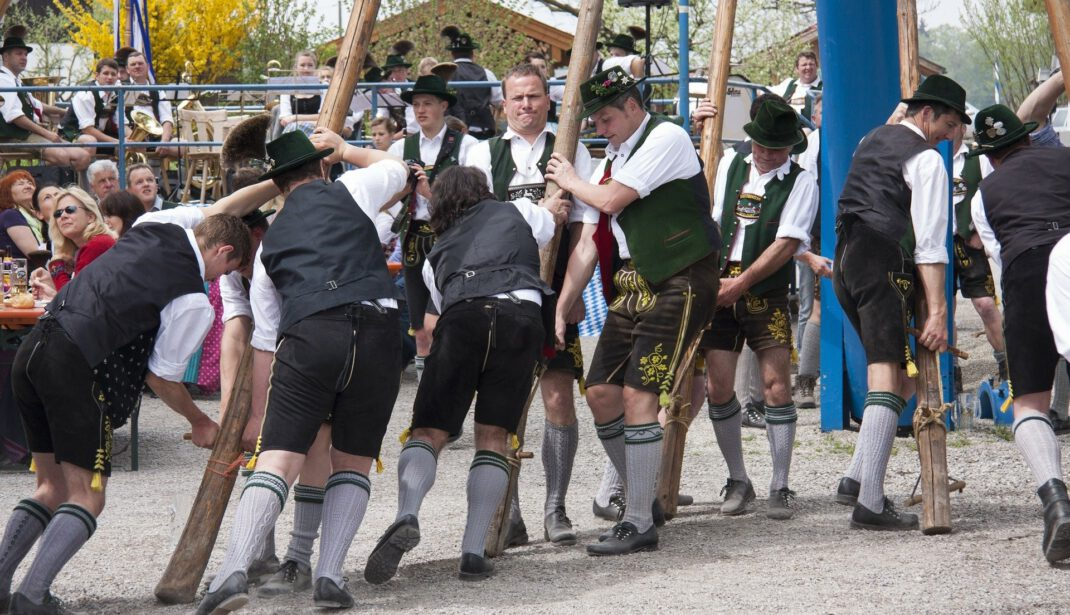 Men in traditional costume setting up maypole
