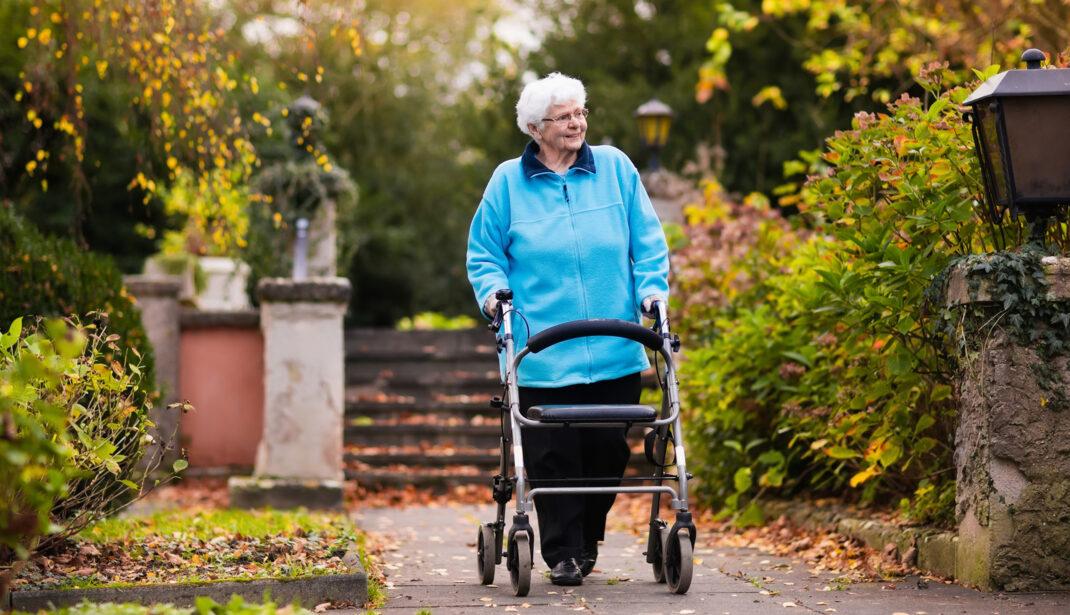 Ältere Dame mit Rollator wartet auf SBS-Senioren-Fahrdienst