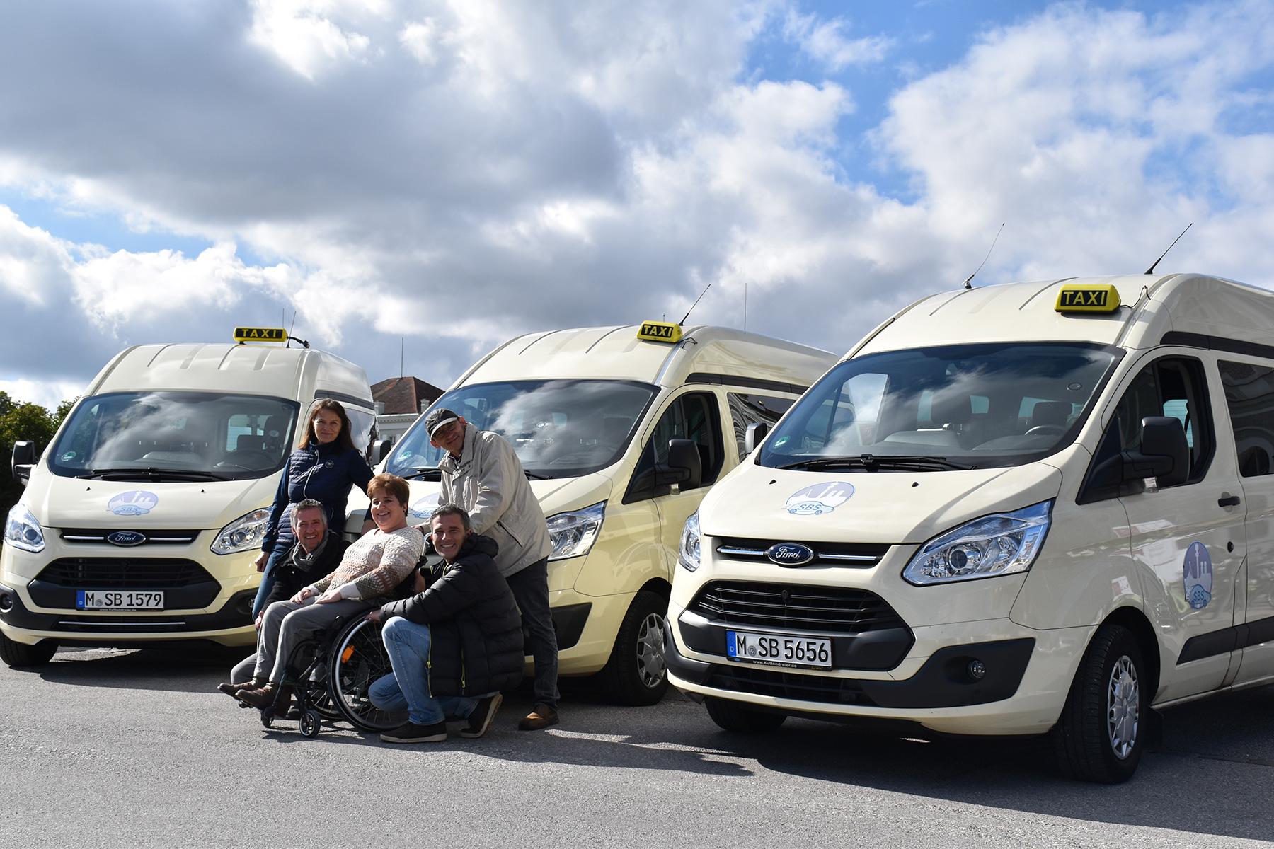 SBS Taxi-Fuhrpark -davor steht eine Rollstuhlfahrerin und vier Begleitern