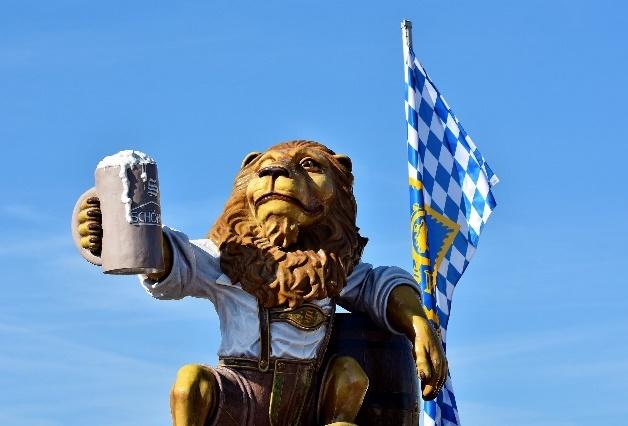 Hofrbräuhaus Löwe mit einem gefüllten Krug in der Hand, hinter ihm ein leeres Fass einer Fahne vpm Hofbräu.