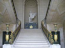 Weiße Marmortreppe steil aufsteigend zu einer einer mannshohen Figur in runder Wandnische