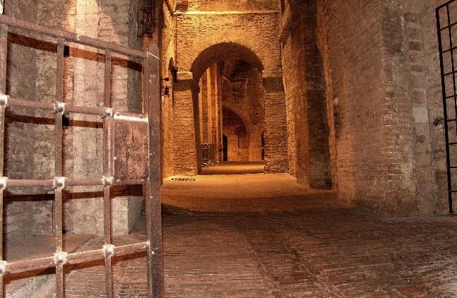 Ziegelgemauerter Kellergang mit Nischen unter Tage mit Eisengitter am Eingang