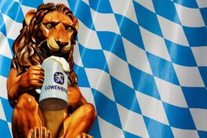Sculpture of a lion with a beer mug in front of the white-blue diamonds of the Bavarian flag