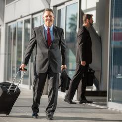 Geschäftsmann mit Koffer wartet auf das Taxi am Flughafen