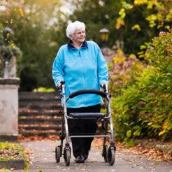 Ältere Dame mit Rollator in München wartet auf SBS-Senioren-Taxi
