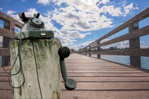 telefon auf holzpflock am steg aufs meer
