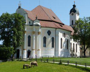 Wieskirche Außenaufnahme im Sonnenlicht mit 2 Pferden auf der Wiese